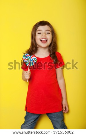 Adorable girl licking lollipop, on yellow background - stock photo