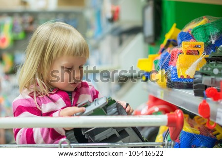 Adorable girl look to toys sit in shopping cart in supermarket - stock photo