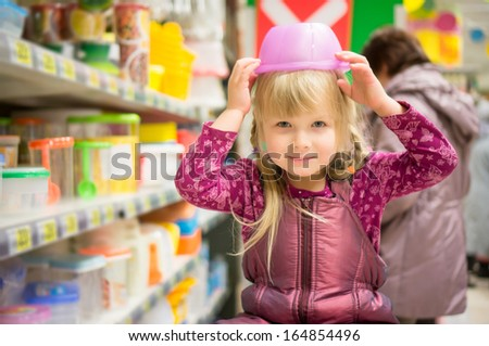 Adorable girl play with plastic containers on head in supermarket