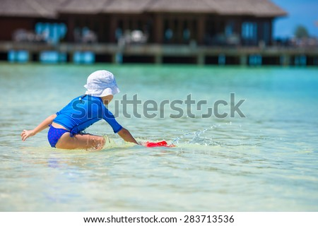 Adorable girl playing with beach toys during tropical vacation