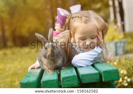 Adorable girl posing on bench with cute rabbit - stock photo