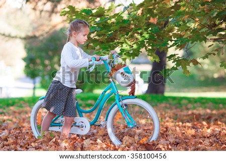 Adorable girl riding a bike at warm autumn day outdoors - stock photo