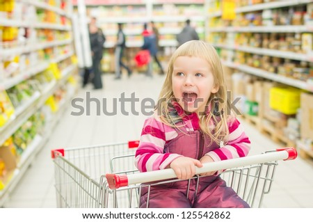 Adorable girl screaming in shopping cart in supermarket