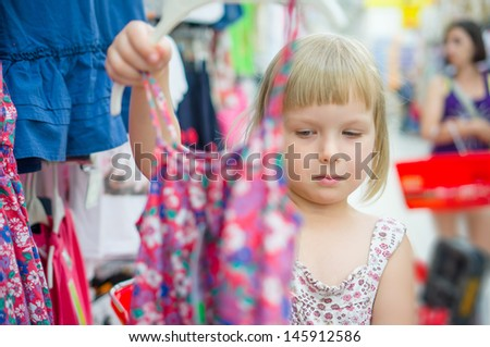 Adorable girl select light dresses in cloth department in supermarket