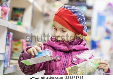 Adorable girl select toys on shelves in supermarket - stock photo