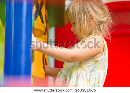 Adorable girl set up circle puzzle on kids playground - stock photo