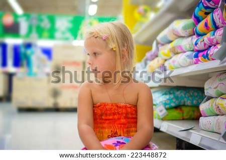 Adorable girl sit on floor near pillow shelves in department section - stock photo