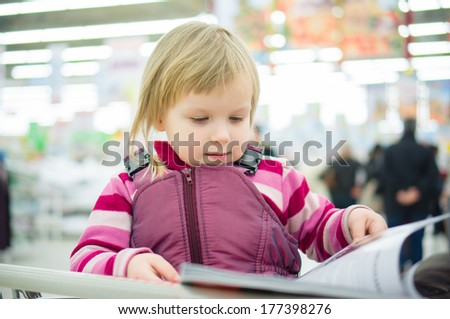 Adorable girl sit on shopping cart and read magazine in supermarket