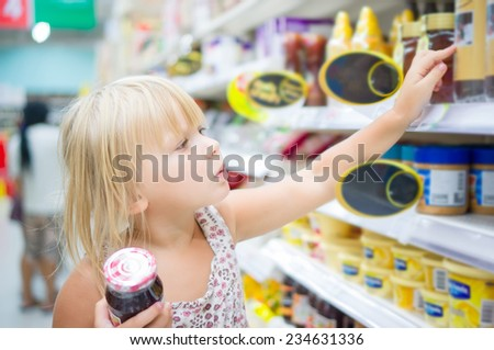 Adorable girl sit with set of good in shopping cart in supermarket - stock photo