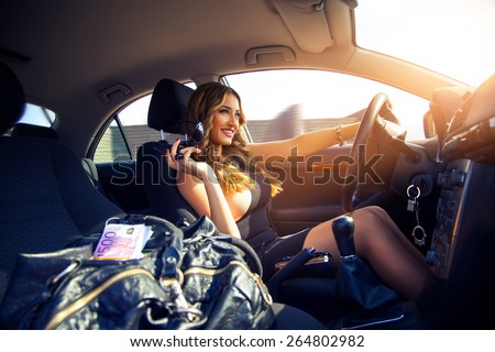 adorable girl smiling and drives a car with a bag full of money in the passenger seat. Inside car photo - stock photo