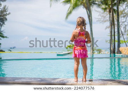 Adorable girl stay at side of swimming pool in tropical beach resort with ocean on back - stock photo
