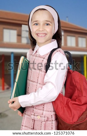 Adorable girl student in the school with a backpack - stock photo