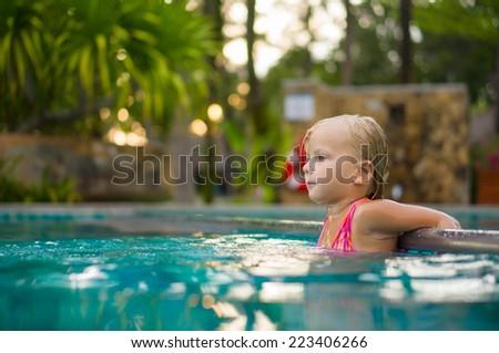 Adorable girl swim in pool at tropical beach resort. Stay at metal pool divider border - stock photo