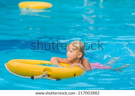 Adorable girl swim in pool with life ring in tropical beach resort - stock photo