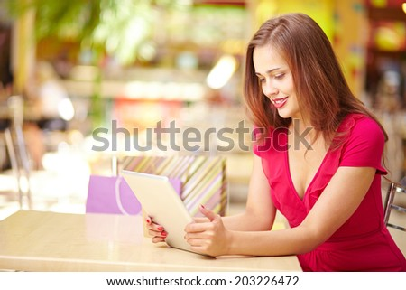 Adorable girl using touchpad after good shopping