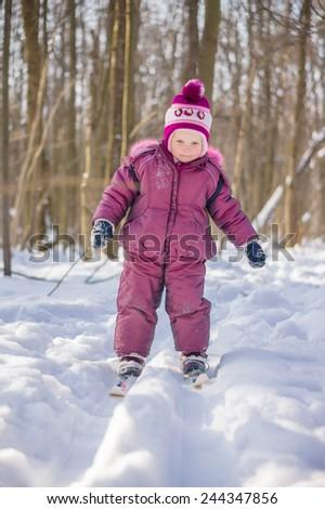 Adorable girl walk on ski in park by ski tracks - stock photo