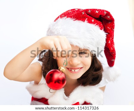 Adorable girl wearing santa claus hat playing with a christmas ball - stock photo