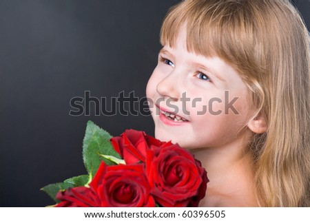 adorable girl with a bouquet of red roses on the studio black background - stock photo