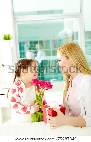 Adorable girl with bunch of beautiful tulips looking at her mother with giftbox - stock photo