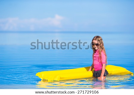 Adorable girl with inflatable mattress in outdoor swimming pool - stock photo