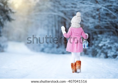 Adorable girl with lamp and candle in winter on Xmas eve outdoors - stock photo