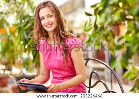 Adorable girl with touchpad sitting in the mall and looking at camera - stock photo