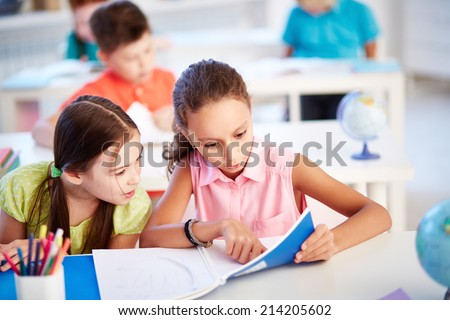 Adorable girls discussing something in copybook at lesson - stock photo