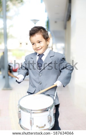 Adorable handsome little boy dressed in a stylish jacket and gloves playing a drum outdoors in a band or during a ceremony at a special event with a proud smile - stock photo