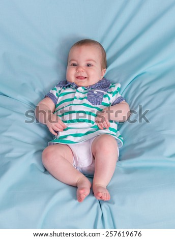 Adorable happy baby boy on blue background.Focus on the face - stock photo