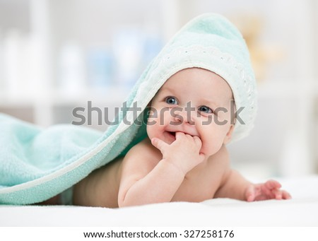 Adorable happy baby child smiling under towel after bathing - stock photo
