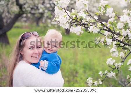 Adorable happy baby girl with mother  in a beautiful blooming fruit garden with white blossoms on apple trees  - stock photo