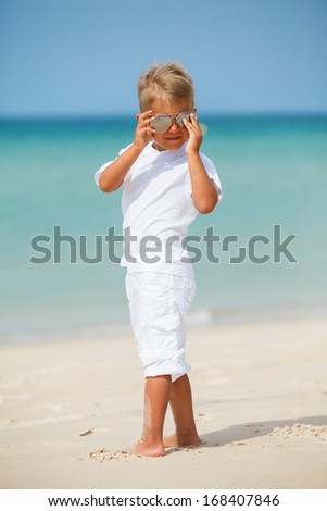 Adorable happy boy in sunglasses on beach vacation - stock photo