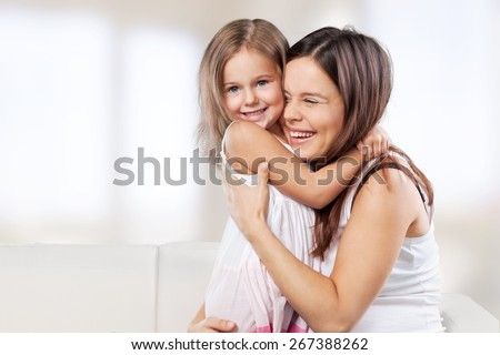 Adorable. Happy family. Mother and baby daughter plays, hugging, kissing at home on the sofa - stock photo
