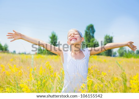 Adorable happy girl in yellow flowers field. Summer freedom andjoy concept.