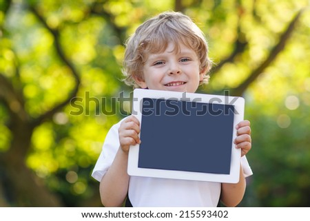 Adorable happy little child holding tablet pc, outdoors. Preschool boy learning with modern technology. - stock photo