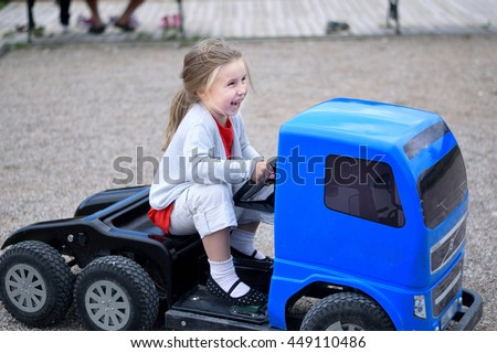 Adorable happy little girl blue electric truck in park on summer day