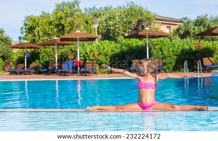 Adorable happy little girl in the swimming pool sitting on the splits - stock photo