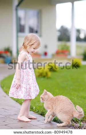 Adorable happy preschooler girl and a cat outdoors - stock photo
