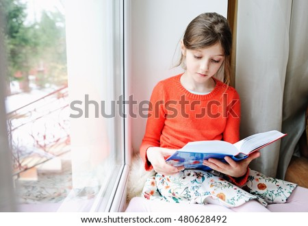 Adorable happy school aged girl reading book on the window in winter cold day
