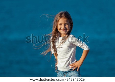 Adorable happy smiling little girl on beach vacation. jeans - stock photo