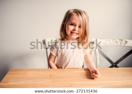 adorable happy toddler girl having fun at home in the kitchen - stock photo