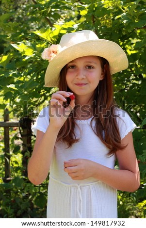 Adorable happy young girl in a white dress and hat standing in the summer garden and posing for the camera