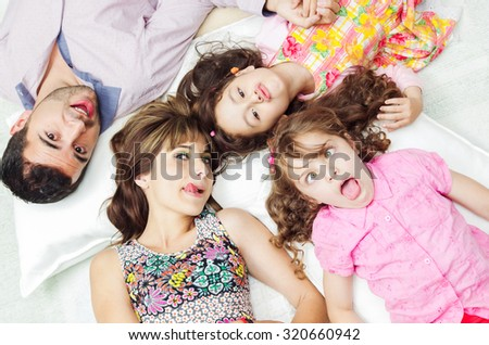 Adorable hispanic family lying down with heads touching showing facial expressions to camera, shot from above angle. - stock photo