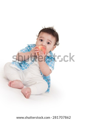 Adorable Indian baby boy eating apple over white background - stock photo