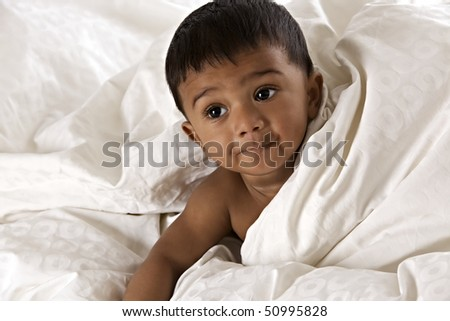 Adorable Indian baby lying on floor covered by a soft blanket and peeping out, isolated on white background. - stock photo