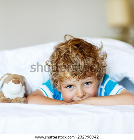 Adorable kid boy after sleeping in his white bed with toy. Square format.