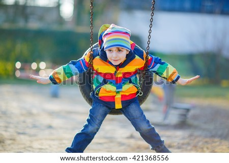 Adorable kid boy having fun with chain swing on outdoor playground. child swinging on warm sunny spring or autumn day. Active leisure with kids. Boy wearing colorful clothes - stock photo