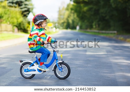 Adorable kid boy in red safety helmet and colorful raincoat riding his first bike on summer day.