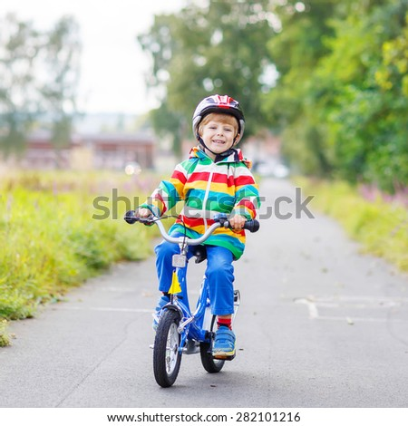 Adorable kid boy in red safety helmet having fun on his first bicycle on summer day. Active leisure for children outdoors.