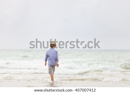 Adorable kid boy in straw hat and sun glasses walking on ocean beach and playing with waves. Vacations by the sea. Outdoor.